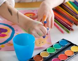 Imagem das mãos de uma criança desenhando em uma folha de papel rosa com tintas e lápis coloridos.