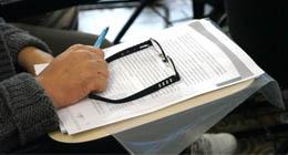 Na imagem, um óculos apoiado em anotações para a preparação de aulas.